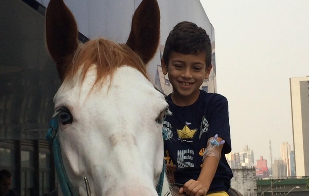 Yuri Maia, 7 anos, não queria mais voltar para o quarto depois de cavalgar por estacionamento de hospital durante visita da égua Lady Bela — Foto: Glauco Araújo/G1