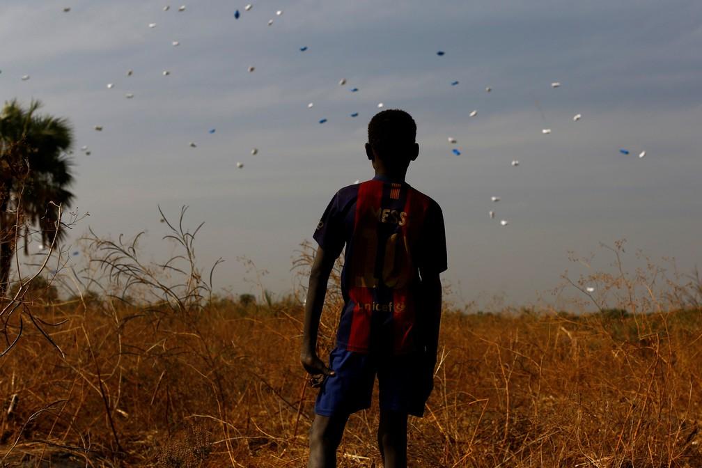 Garoto observa paraquedas com alimentos da ONU caindo perto da vila de Rubkuai, no norte do Sudão do Sul (Foto: Siegfried Modola/Reuters)