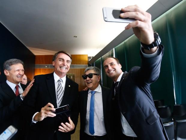 De férias e à paisana, o policial federal Newton Ishii posa para fotos com os deputados Eduardo Bolsonaro (PSC-SP) e Jair Bolsonaro (PP-RJ) durante visita ao plenário da Câmara dos Deputados, em Brasília (Foto: Dida Sampaio/Estadão Conteúdo)