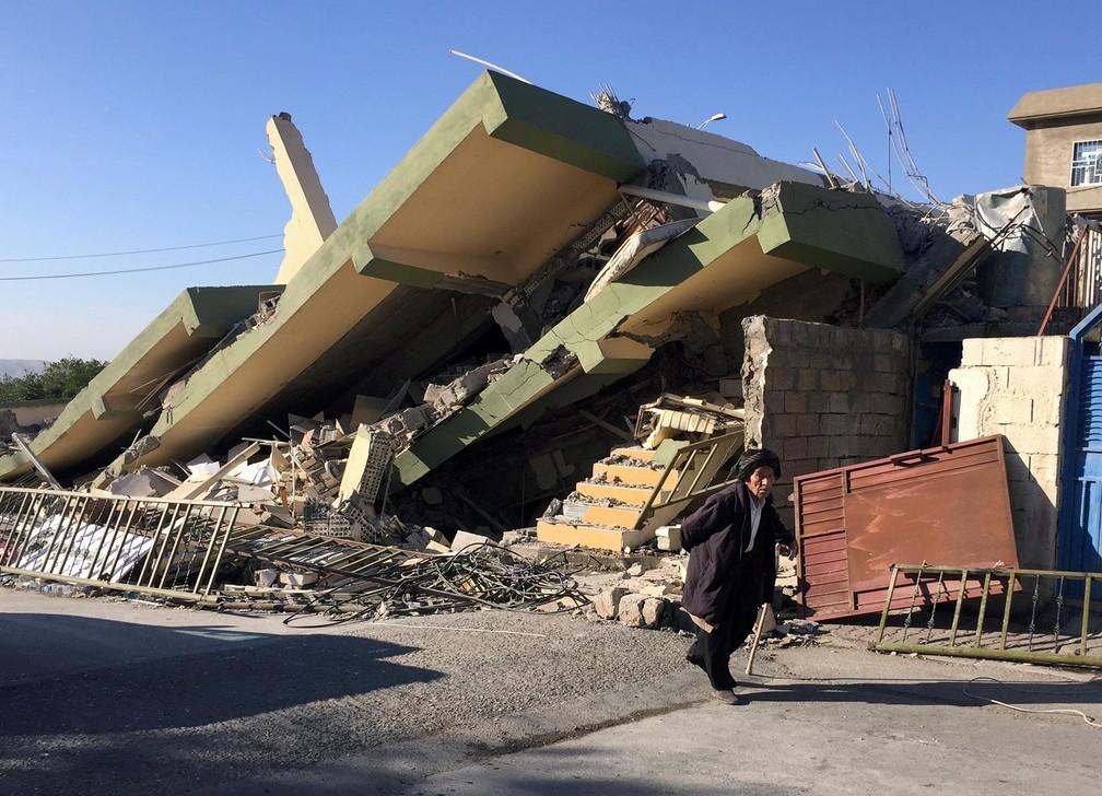 Homem caminha entre prédios destruídos por terremoto em Darbandikhan, no Iraque (Foto: Ako Rasheed/Reuters)