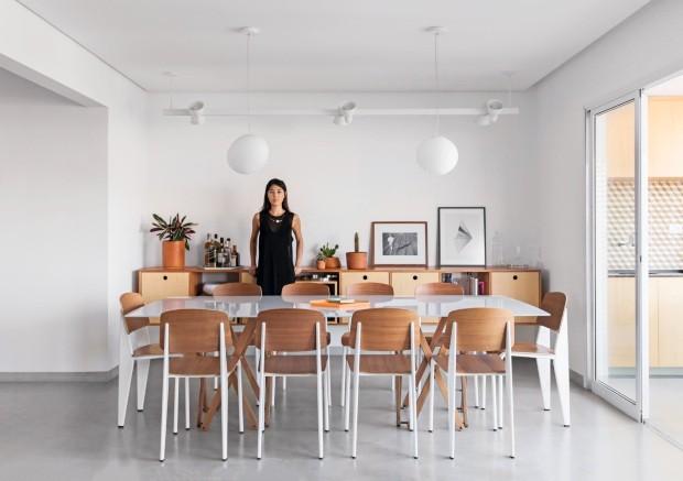 SALA DE JANTAR | Liz posa diante do aparador desenhado pelo escritório, de freijó lavado com caixas de pinho. A mesa, composta de duas bases da mesa Camelo, da Ovo, e tampo de vidro serigrafado, é acompanhada de cadeiras Standard, de Jean Prouvé, na Artes (Foto: Maíra Acayaba / Editora Globo)