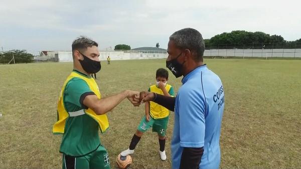 O professor da escolinha, Benevaldo Brito Alves, usa o exemplo de Carlinhos como motivação para os outros alunos — Foto: Claudio Farneres/TVTEM