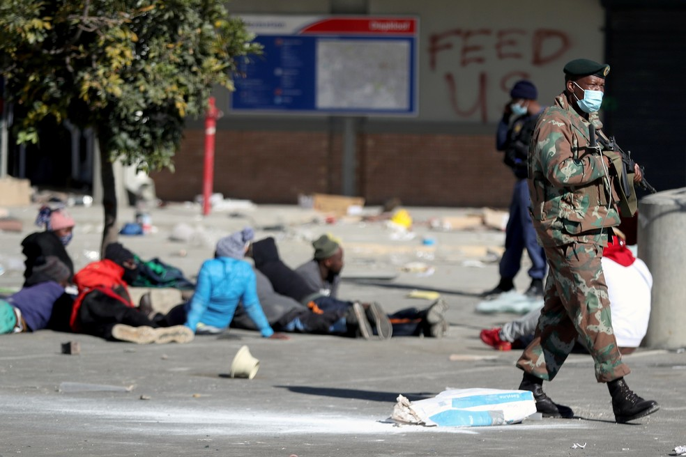 Militar mantém guarda próximo a suspeitos de saque do lado de fora do shopping Diepkloof, em Soweto, nesta terça (13), após à prisão do ex-presidente sul-africano Jacob Zuma — Foto: Siphiwe Sibeko/Reuters
