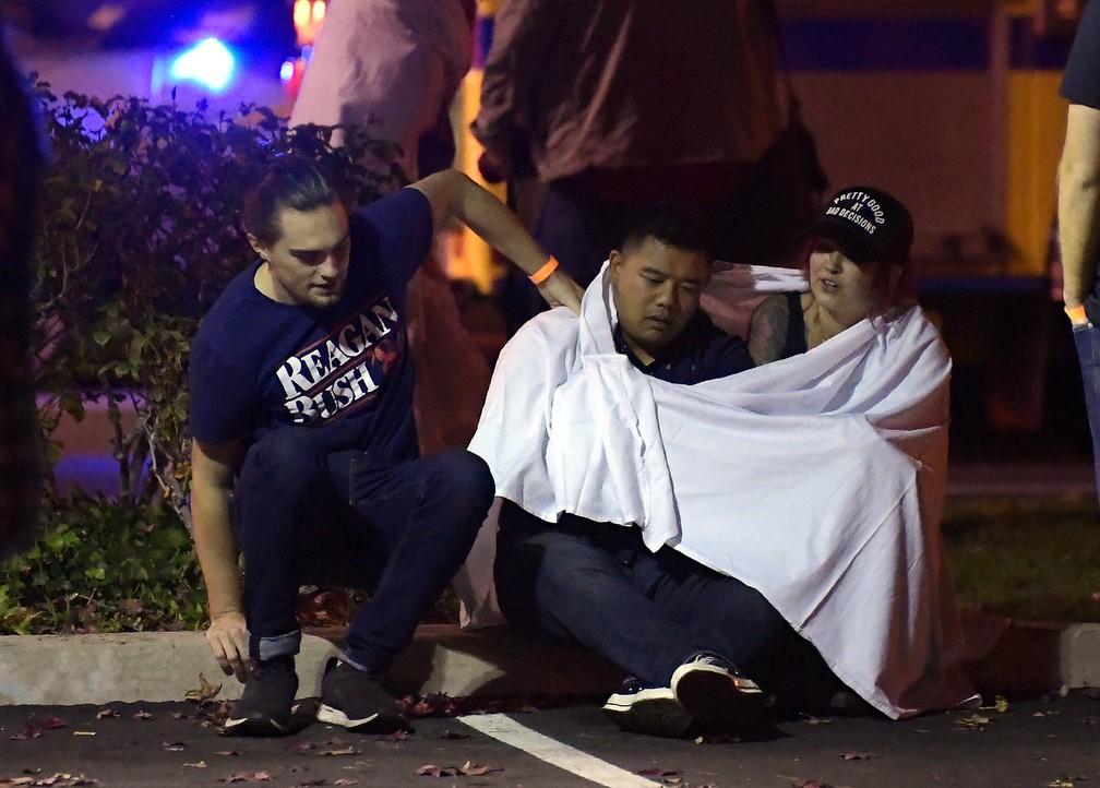 Jovens sentam em rua próxima ao bar em que tiroteio deixou mortos na noite desta quarta-feira (7) na Califórnia — Foto: Mark J. Terrill/AP Photo