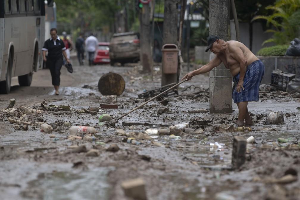 Homem tenta limpar sujeira que se acumulou em sua calçada após temporal em São Conrado, no Rio — Foto: Mauro Pimentel/AFP