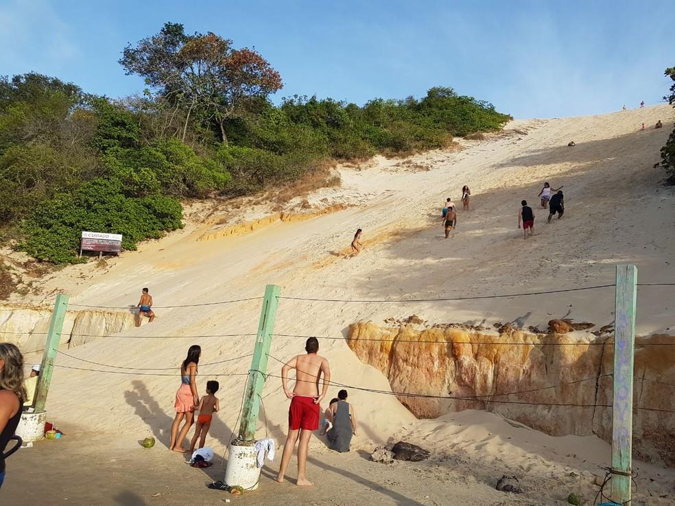 Pessoas sobem indiscriminadamente Morro do Careca, em Natal, que desde 1997 foi cercado para proibir a circulação na área (Foto: Léo Santos/Cedida)