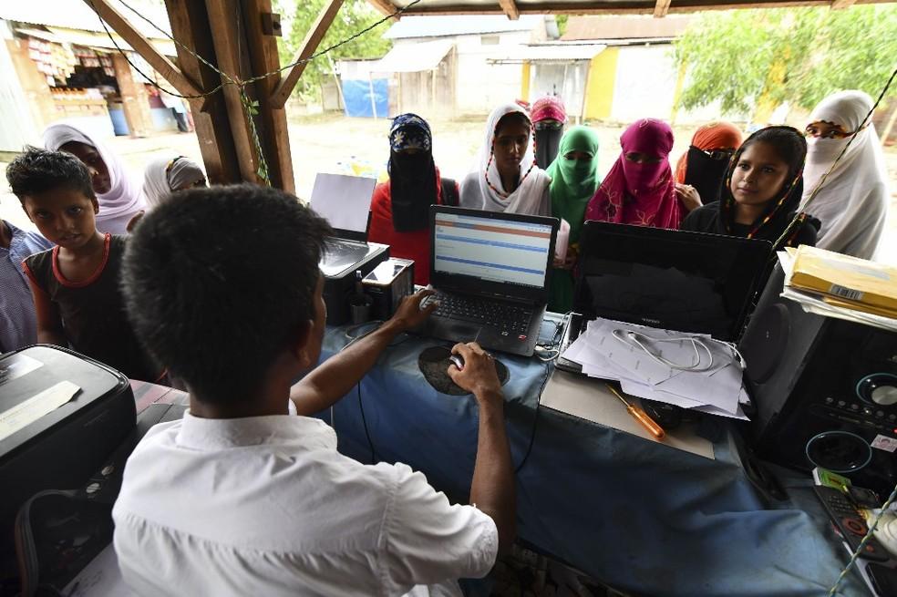 Pessoas checam seus nomes no cadastro NRC, na região de Assam, na Índia — Foto: Biju Boro/AFP