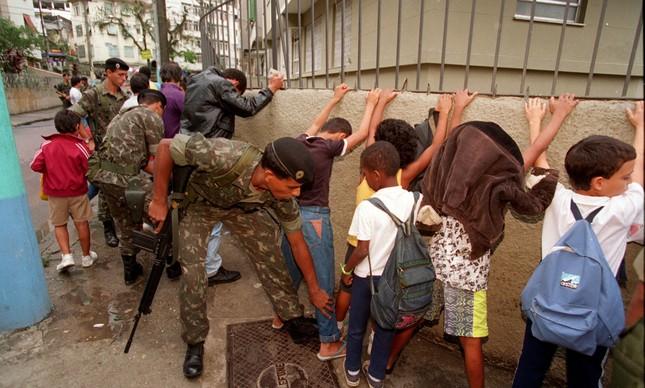 Foto que mostra militares revistando crianças foi tirada em 22 de nvoembro de 1994, na porta de uma escola na favela Dona Marta, em Botafogo, Zona Sul do Rio