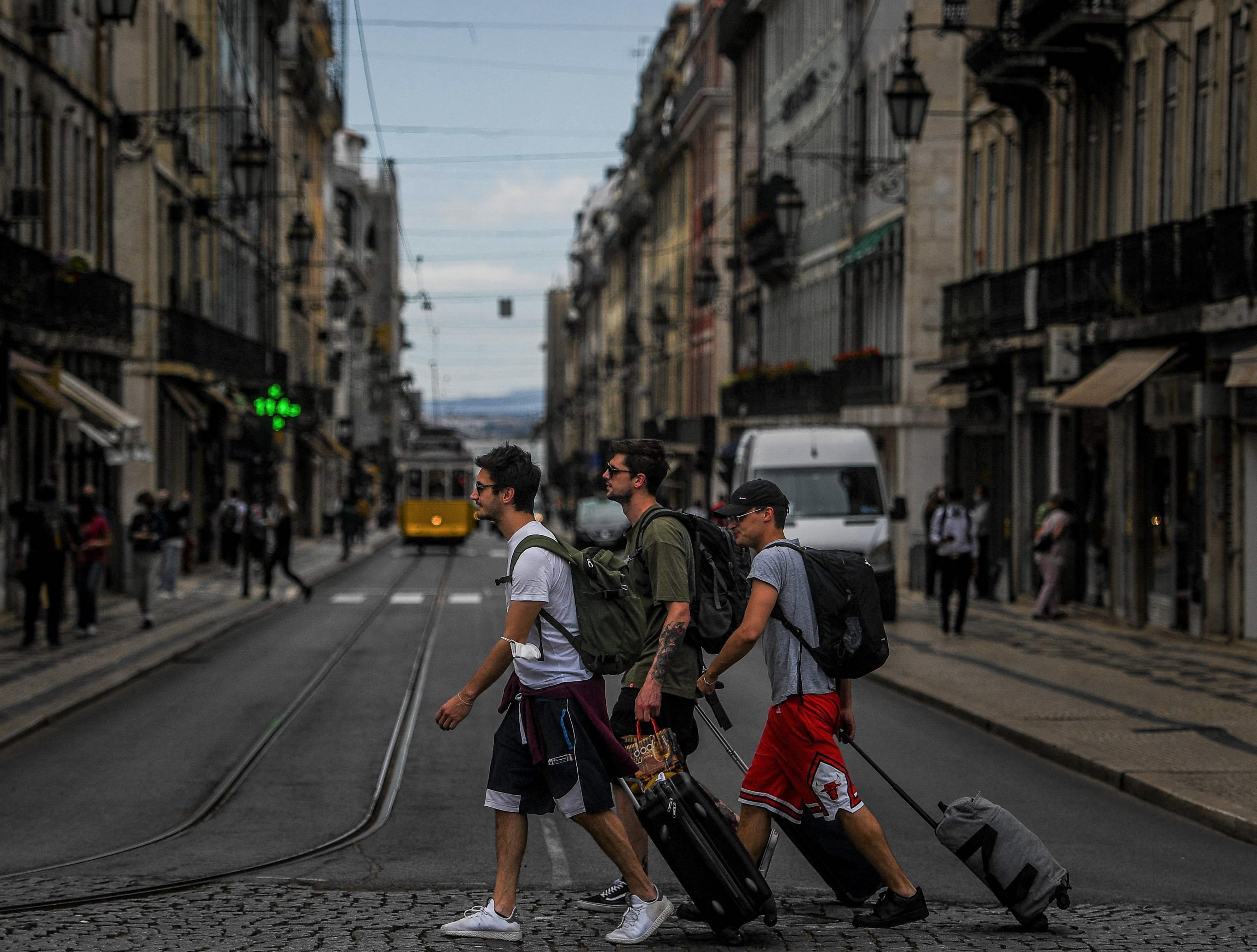 Turistas puxam suas malas pelas ruas de Lisboa
