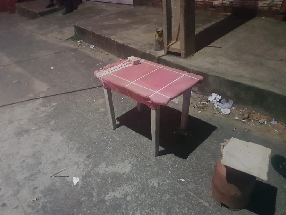 Homem estava jogando baralho em uma mesa próximo a uma calçada quando foi baleado e morto — Foto: Rafaela Duarte/SVM