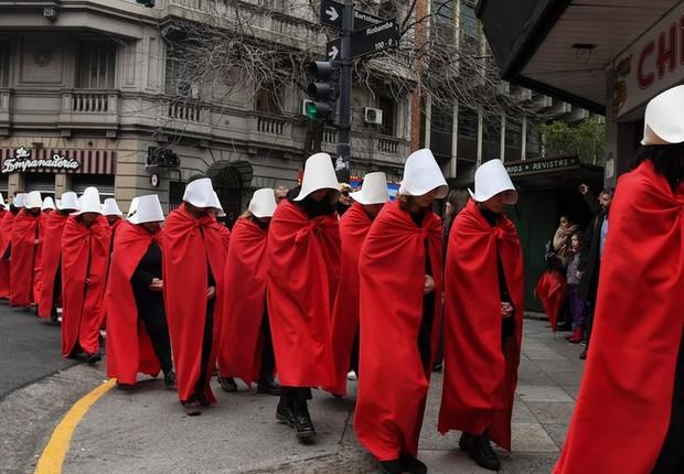 Manifestantes argentinas usam como símbolo as cores e vestimentas de personagens da ficção científica de Margaret Atwood, escrita em 1985 (Foto: AFP Via BBC News Brasil)