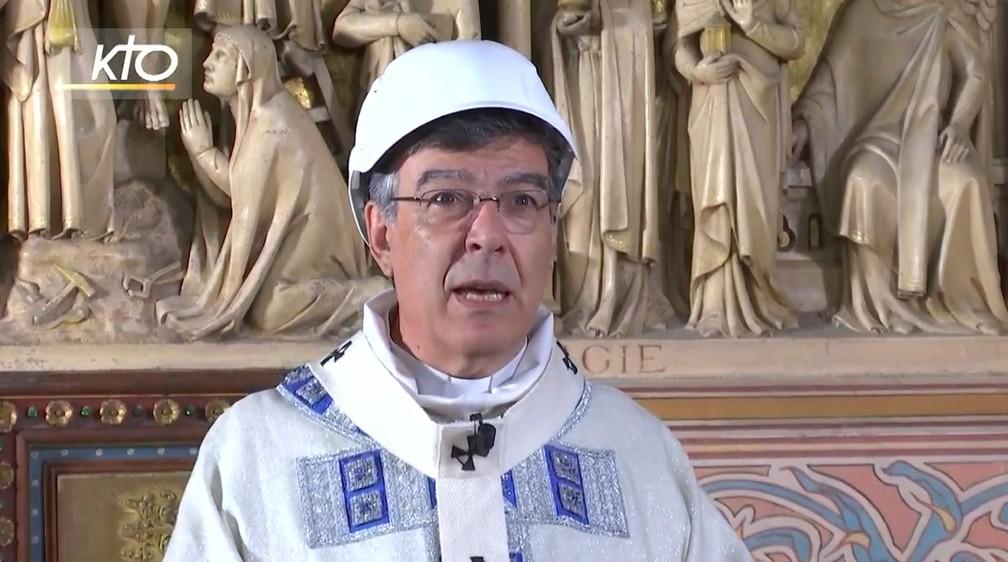 O arcebispo de Paris Michel Aupetit, que celebrou a primeira missa na Catedral de Notre-Dame com um capacete de segurança — Foto: Reprodução/KTOTV