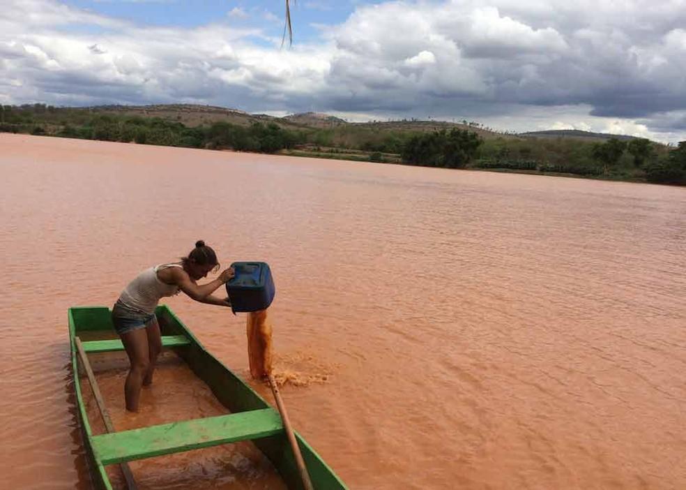 Agricultora tira água enlameada de barco no Rio Doce em Baixo Guandu, ES — Foto: Flávia Mantovani/ Arquivo G1