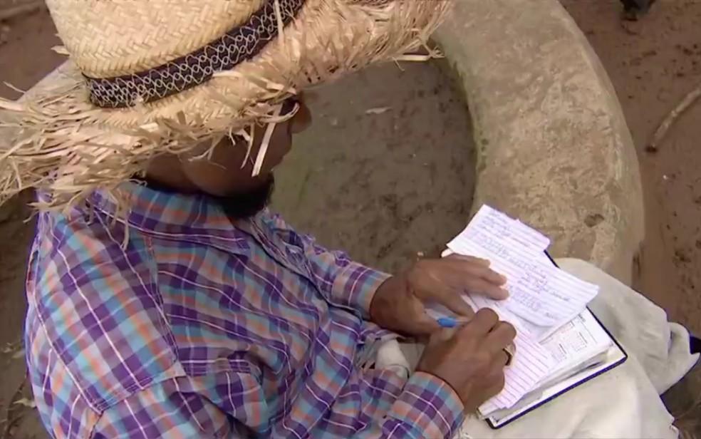 Marcos Reis escreve currículos à mão para entregar em Senador Canedo, Goiás — Foto: Reprodução/TV Anhanguera
