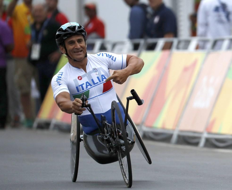 Descrição: Zanardi aponta para o nome da Itália em seu uniforme ao fim da corrida — Foto: REUTERS/Ricardo Moraes