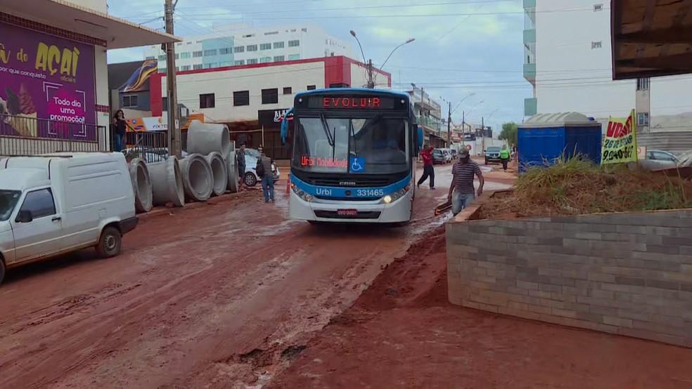 Coletivos passam por rua 4A, em Vicente Pires, , no DF, com velocidade reduzida devido ao acúmulo de lama após a chuva  — Foto: Reprodução/TV Globo