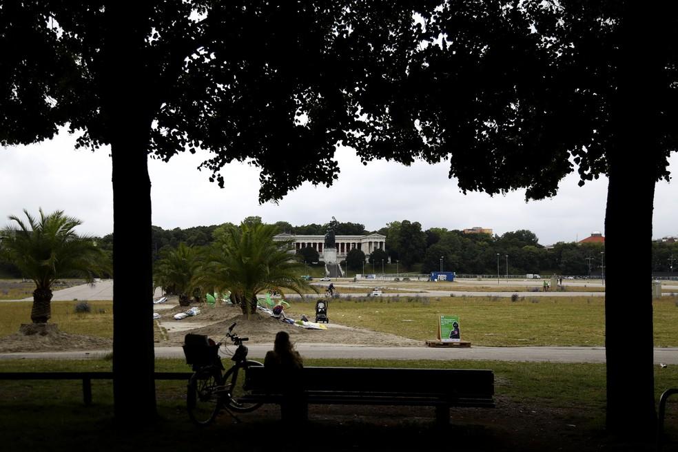 Mulher senta em um banco no espaço em que seria realizado o Oktoberfest, uma das festas mais famosas da Alemanha. Normalmente, a construção para o festival começa em julho, em Munique. Por causa da pandemia, o evento deste ano foi cancelado.  — Foto: Matthias Schrader/AP