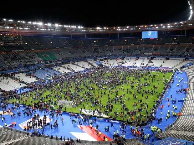 Público no campo do Stade de France após a série de ataques (Foto: Michel Euler/AP)