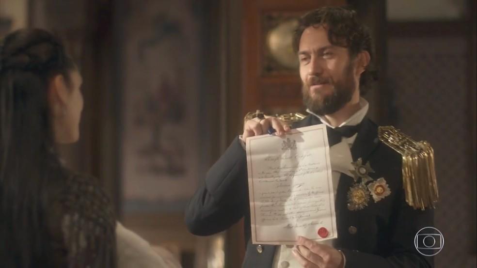 Thomas (Gabriel Braga Nunes) mostra a Anna (Isabelle Drummond) registro de nascimento de Vitoria, em 'Novo Mundo' — Foto: TV Globo