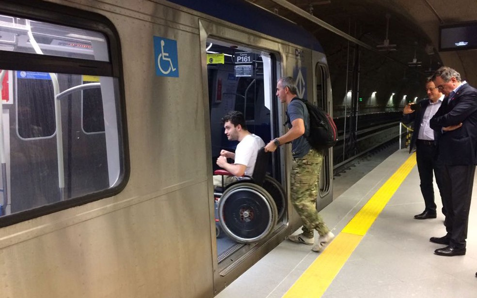 Marco coloca o filho Rafael dentro do vagão; vão entre plataforma e trem tem desnível (Foto: Marina Pinhoni/G1)