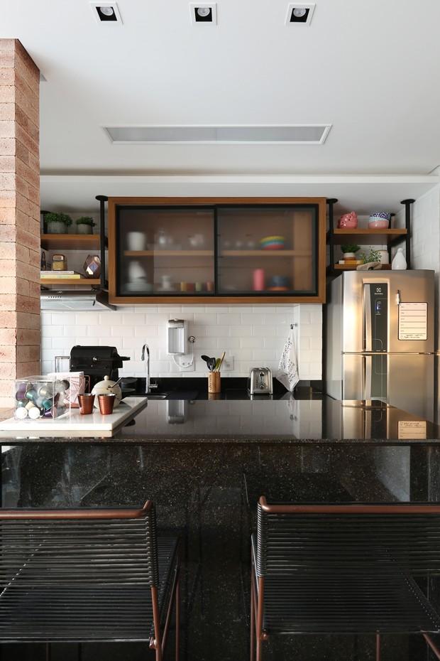 COZINHA | A cozinha foi integrada com a área social para dar mais espaço ao ambiente. Revestimentos da Texthura y Cor. Banquetas de Fernando Jaeger (Foto: Mariana Orsi  / Divulgação)