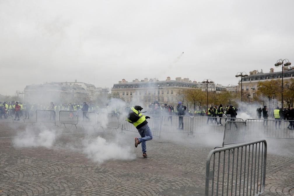 Manifestante de colete amarelo lança gás contra a polícia neste sábado (1) na avenida Champs-Elysées, em Paris. O protesto é contra o aumento de impostos do governo Macron. — Foto:  Kamil Zihnioglu/AP