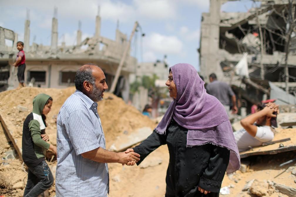 Palestinos apertam as mãos após retornarem para suas casas destruídas, em Beit Hanoun, no norte da Faixa de Gaza — Foto: Mohammed Salem/Reuters