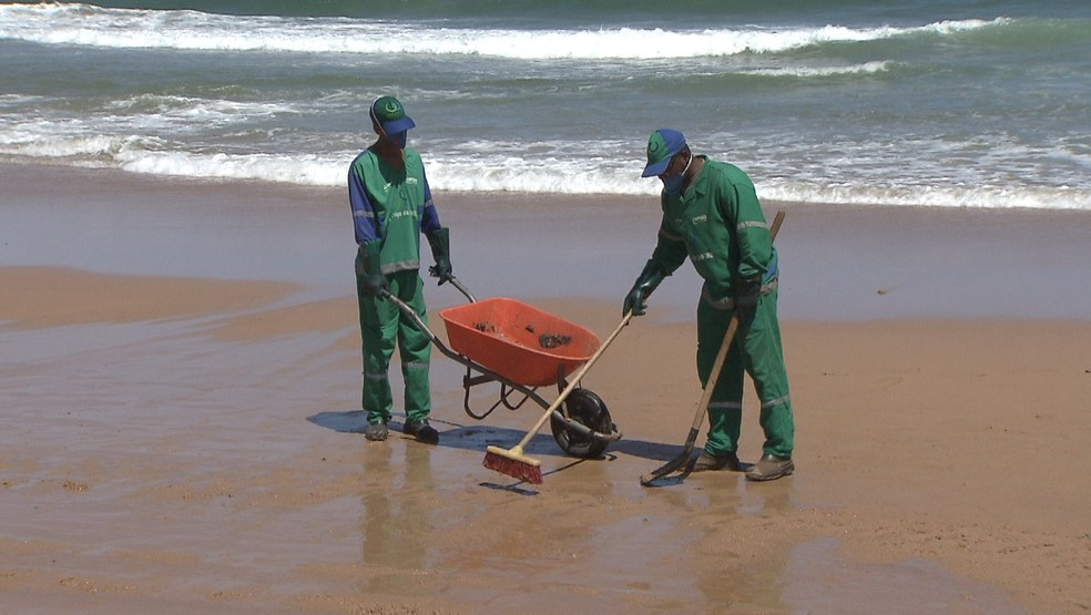 Equipes da Limpurb limparam manchas de óleo que voltaram a aparecer na praia de Stella Maris, em Salvador, na sexta-feira — Foto: Reprodução/TV Bahia