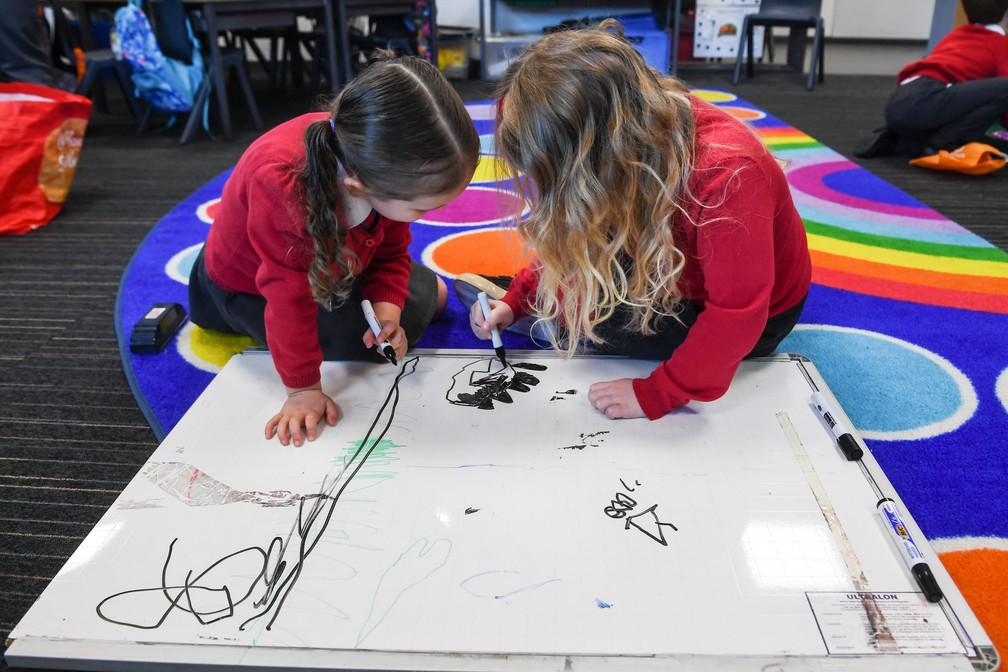 Meninas brincam no primeiro dia de retorno às aulas presenciais em uma escola primária de Glasgow, na Escócia, no dia 22 de fevereiro. — Foto: Andy Buchanan/AFP