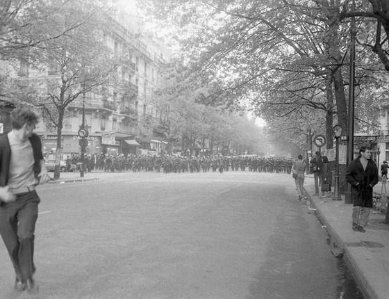 Jovem corre de forças policiais no Boulevard Saint-Michel, em Paris (Foto: Philippe Gras)
