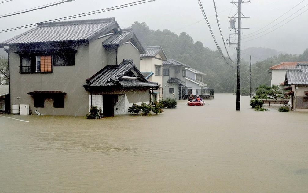 Equipes de resgate em um barco patrulham a área residencial inundada pelo tufão Hagibis, em Ise — Foto: Kyodo / via AP Photo