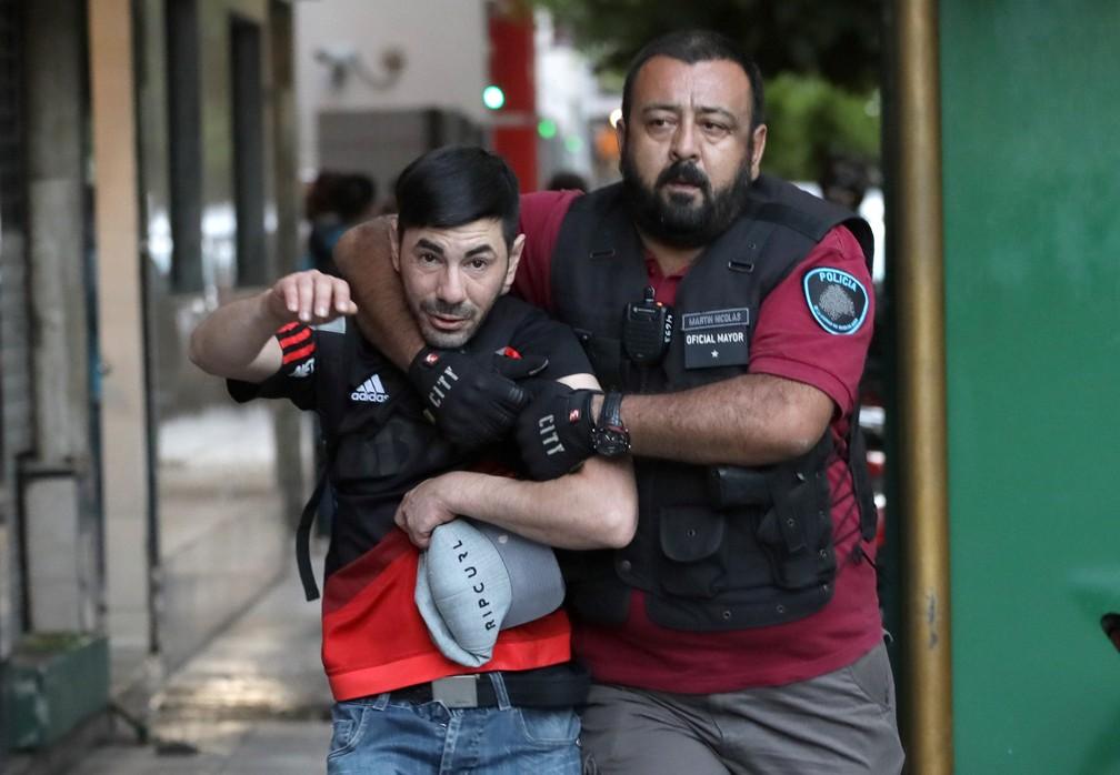 Um torcedor do River Plate é detido por um policial após confrontos nas ruas de Buenos Aires — Foto: Alberto Raggio/Reuters
