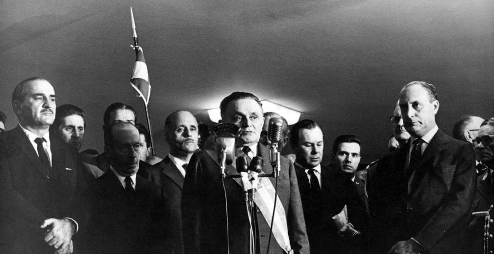 Castelo Branco (ao centro, diante dos microfones) assume a presidência; um pouco mais à direita, de mãos cruzadas, está Ranieri Mazzilli, e imediatamente atrás deste, olhando para frente, mas encoberto, está o General Ernesto Geisel — Foto: Arquivo/O Globo