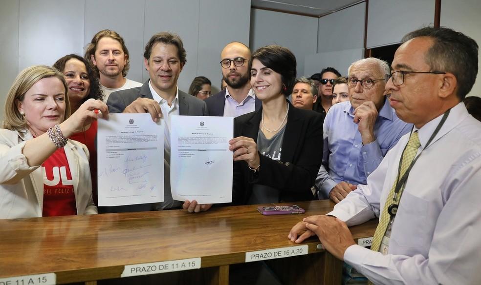 Gleisi Hoffmann (presidente do PT), Fernando Haddad e Manuela D'Ávila exibem registro da candidatura de Lula entregue ao TSE (Foto: Nelson Jr./ASCOM/TSE )