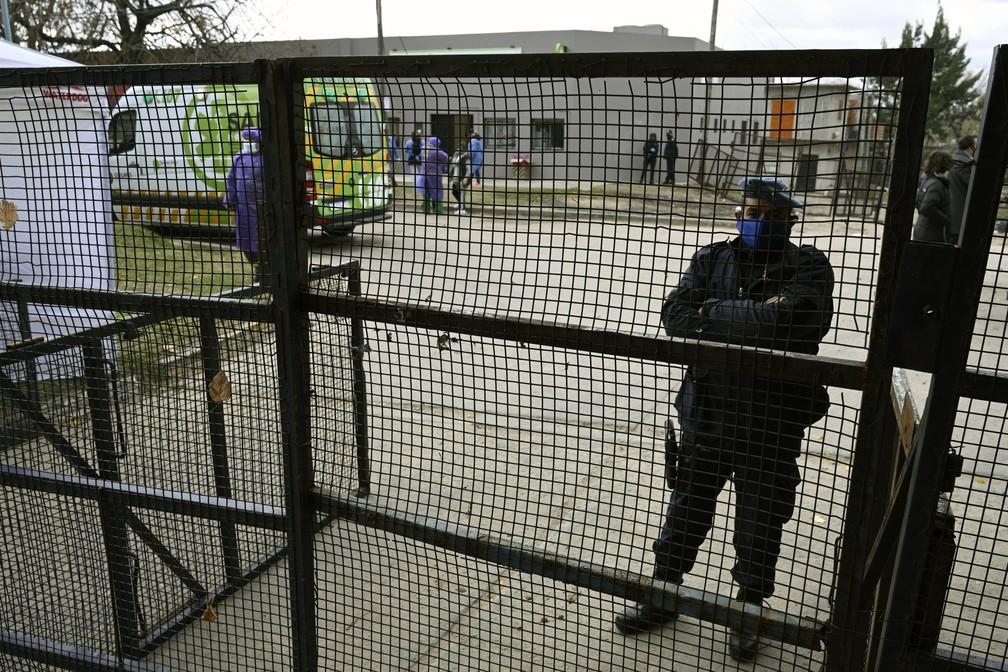 Policial vigia cerca montada ao redor de bairro na periferia de Buenos Aires, na Argentina — Foto: Juan Mabromata/AFP