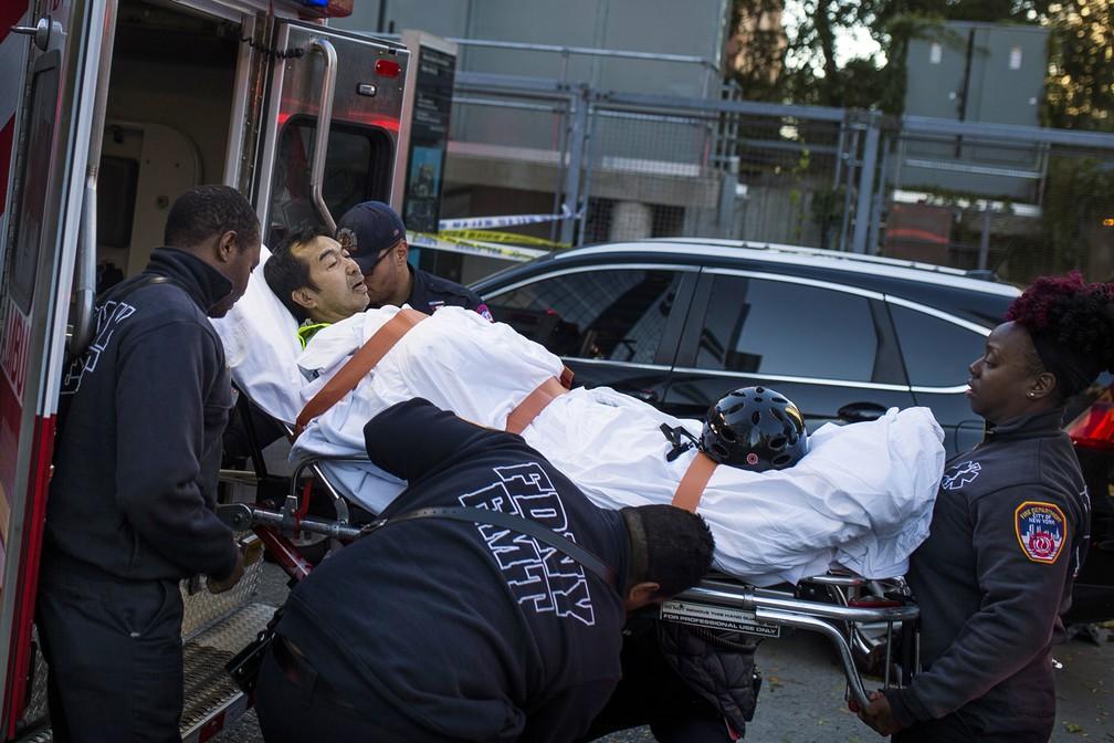 Homem é levado para uma ambulância após ficar ferido em atentado em ciclovia nesta terça-feira, em Nova York (Foto: Andres Kudacki/AP)