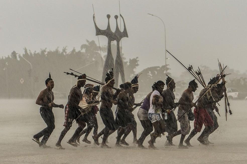 Índios correm da chuva na Praça dos Três Poderes, em Brasília — Foto: Agência Brasil/Valter Campanato