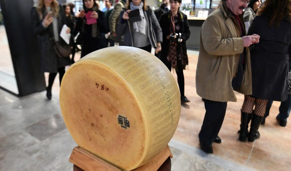 Pessoas caminham ao redor de queijo parmesão original italiano em Bolonha (Foto: Vincenzo Pinto/AFP)