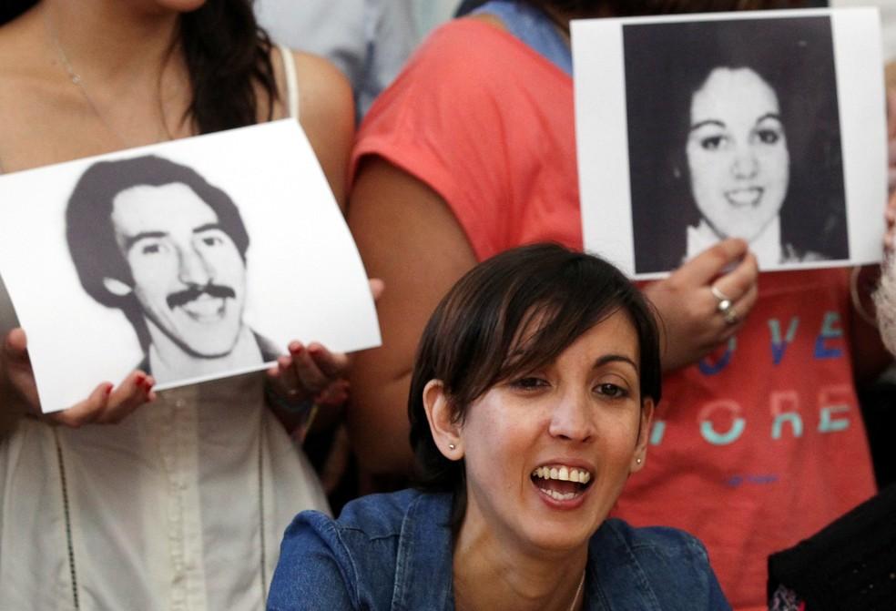 Ativistas seguram fotos dos pais de Adriana, que desapareceram em 1977 (Foto: Bernardino Avila/Reuters)