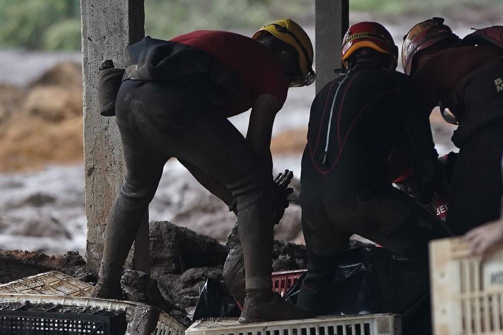 27 de janeiro - Bombeiros retiram corpo da lama depois do rompimento da barragem da Vale, em Brumadinho — Foto: Leo Correa/AP