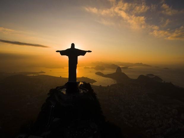 O amanhecer é visto por trás do Cristo Redentor diante da Baía de Guanabara, no Rio de Janeiro (Foto: Felipe Dana/AP)