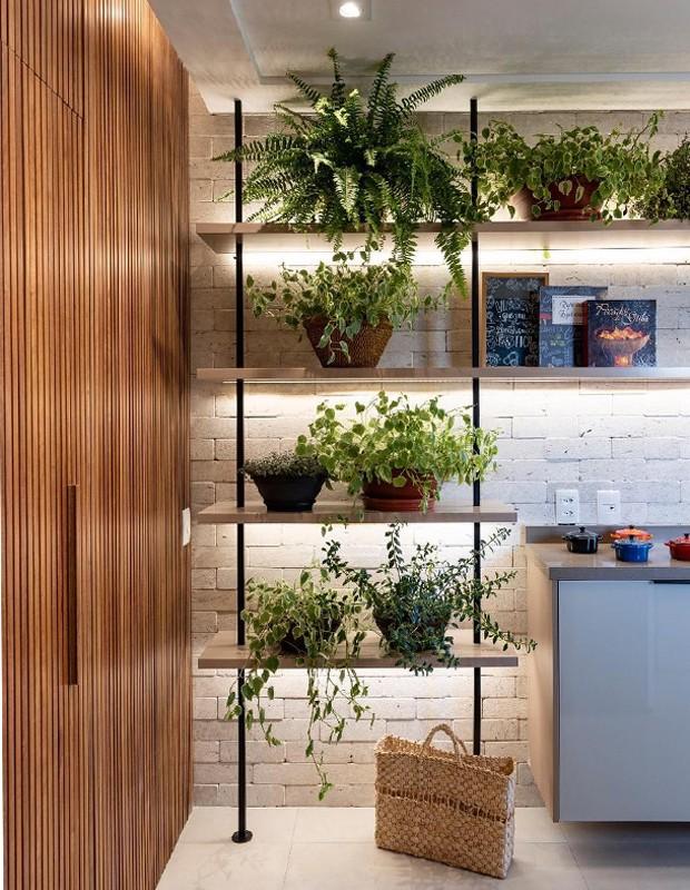 O paisagismo interno funciona como uma extensão do externo, promovendo também a integração de ambientes. No canto direito, um buffet serve como apoio durante os eventos da família.  (Foto: Raul Fonseca/Divulgação)