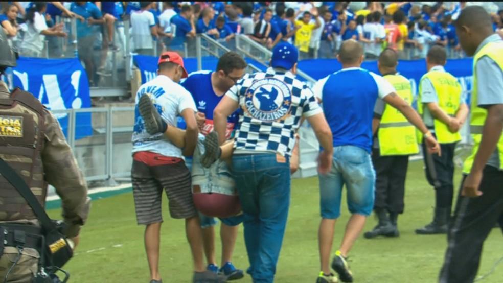 Torcedor do Cruzeiro sai carregado após invadir campo no Mineirão, em Belo Horizonte — Foto: Reprodução/TV Globo