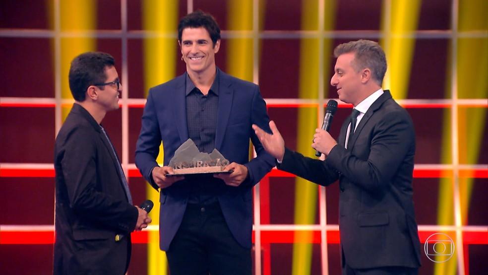 Wagner Moura recebe o prêmio das mãos do padrinho, Reynaldo Gianecchini — Foto: TV GLOBO