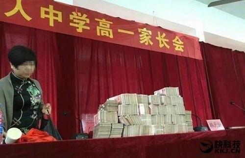Funcionária da escola exibe o dinheiro a ser distribuído aos aprovados