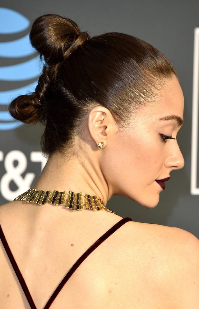 Emmy Rossum chamou atenção pelo batom vinho exatamente da mesma cor do vestido, mas o penteado moderninho, de rabo torcido em coque, deu o arremate perfeito no look. (Foto: Getty Images)