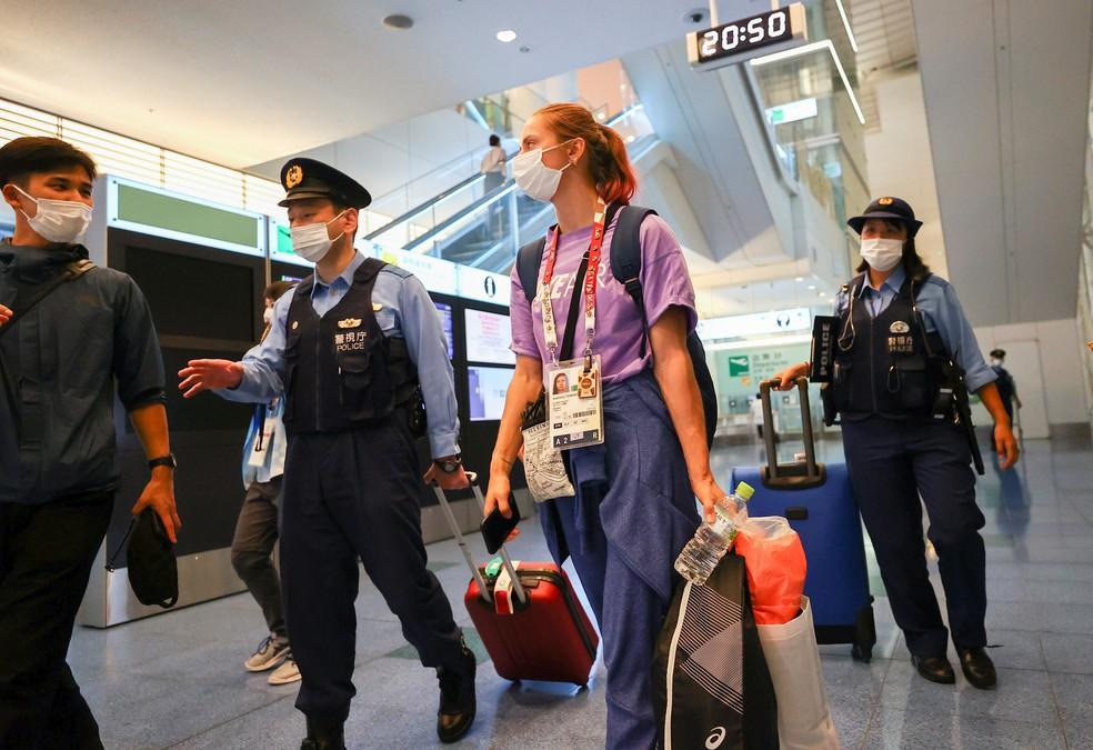 Krystsina Tsimanouskaya é escoltada por policiais no aeroporto de Tóquio, em 1º de agosto de 2021 — Foto: Issei Kato/Reuters
