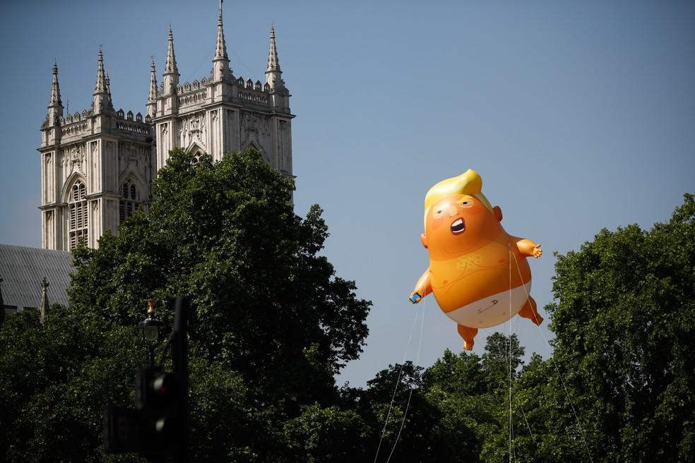 Boneco inflável do presidente dos EUA Donald Trump é visto perto das torres de Westminster Abbey em Londres, na Inglaterra, durante um protesto contra a visita de Trump ao país (Foto: Tolga Akmen/AFP)