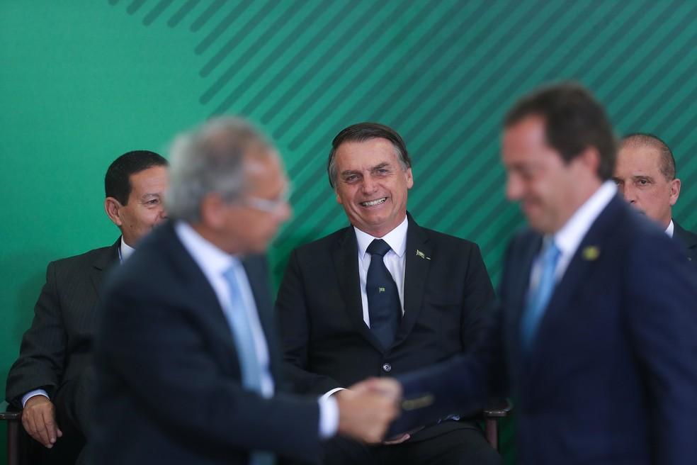 Paulo Guedes cumprimenta Pedro Guimarães, presidente da Caixa, sob o olhar de Bolsonaro — Foto: Bruno Spada/Tripé Imagem/Estadão Conteúdo