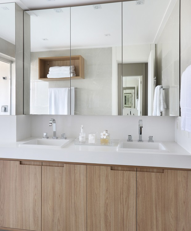 Casa e banho   Originalmente, o banheiro era menor, mas ganhou mais espaço para o encaixe de dois chuveiros. O mdf do living também aparece nos gabinetes (Foto: Mariana Orsi/ Divulgação)